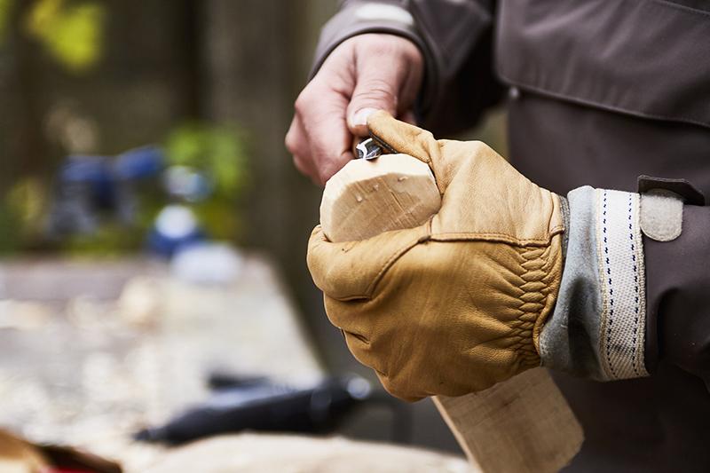 Bearbeiten und schälen Sie das Ende des Holzstücks mit einem Holzschnitzmesser so, wie Sie einen Apfel schälen würden.