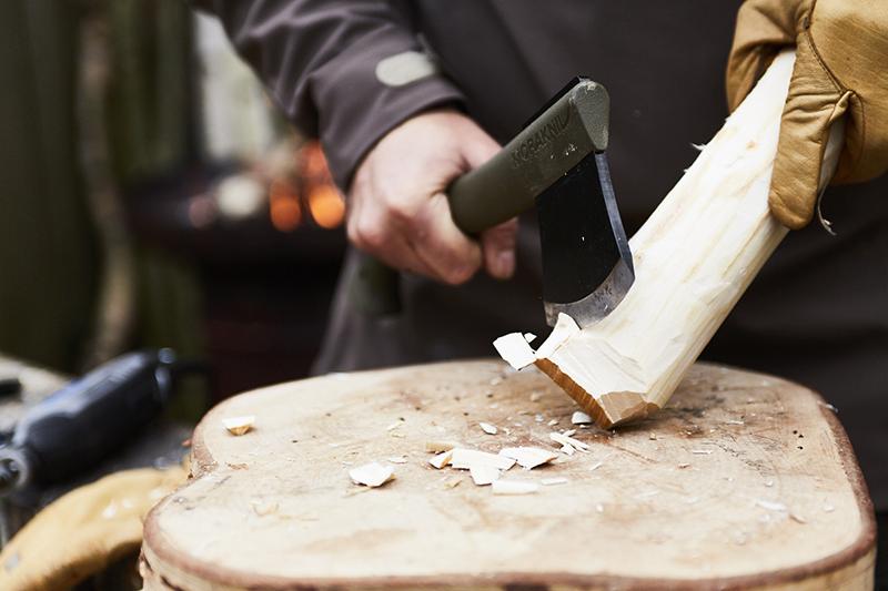 Runden Sie mit einer Axt die Enden des Holzstücks ab.
