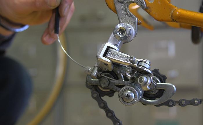 Nimm das Rad heraus, schneide die Kabelendkappe ab und ziehe das Kabel heraus.