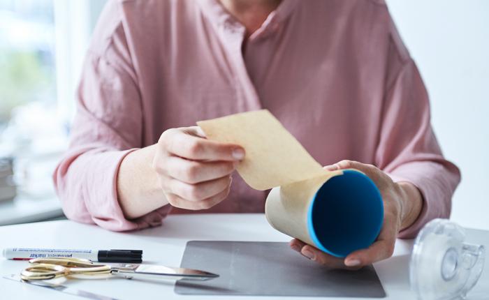 Zum Zeichnen deines Entwurfs für die Kaffeebecherhülle wickelst du zuerst Backpapier um den Becher.