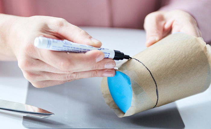 Beim Zeichnen eines Entwurfs auf ein rundes Objekt, wie diesen Mehrweg-Kaffeebecher, kannst du deinen Finger zu Hilfe nehmen, um eine gerade Linie zu erzielen.