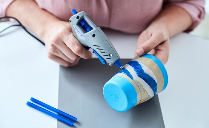 Beginne, mit Kleber aus deiner Klebepistole auf dem Backpapier zu zeichnen.