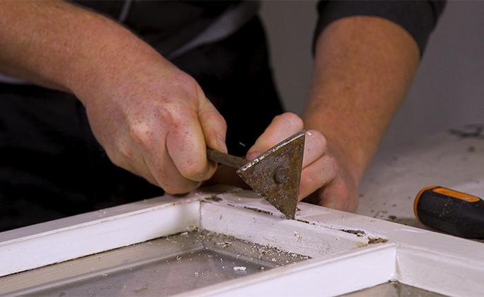 Schleifvorbereitungen: Entferne Holzfäule und alte Farbe mit einem Farbschaber mit Dreiecksklinge.