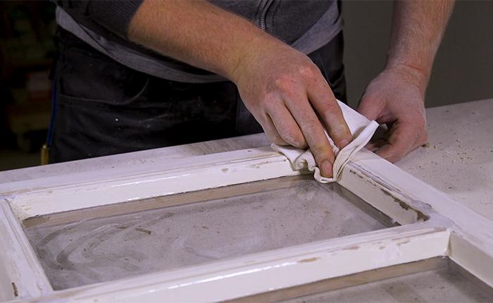 Nach dem Schleifen reinigst du den Fensterrahmen mit einem Entfetter.
