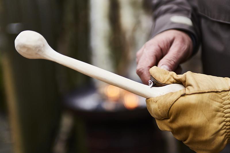 Usando un cuchillo de tallar, empiece a retirar capas muy finas de madera.