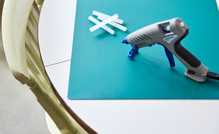 Assurez-vous d'avoir à portée de main tous les éléments essentiels pour le collage: un tapis de création, un pistolet à colle et des bâtons de colle.
