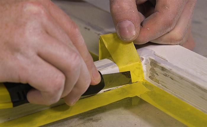 Application d'un ruban de masquage sur le châssis de fenêtre afin de protéger la vitre.