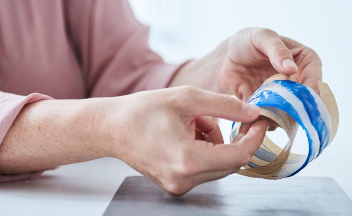 Vegye le a ragasztott újrafelhasználható bögrevédőt a sütőpapírról.