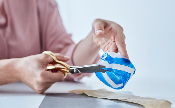 Vágja le a felesleges ragasztót ollóval. Már majdnem el is készült az újrafelhasználható bögrevédővel!