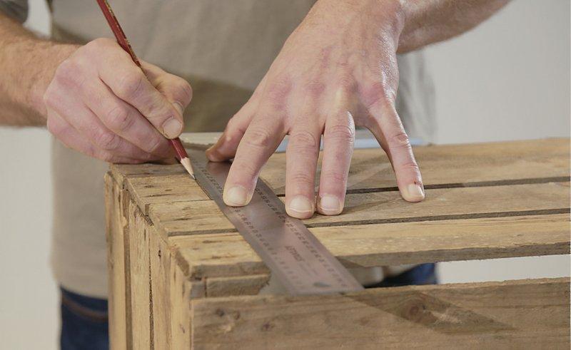 Gebruik een winkelhaak en een potlood om de snijlijnen op elke houten krat aan te duiden