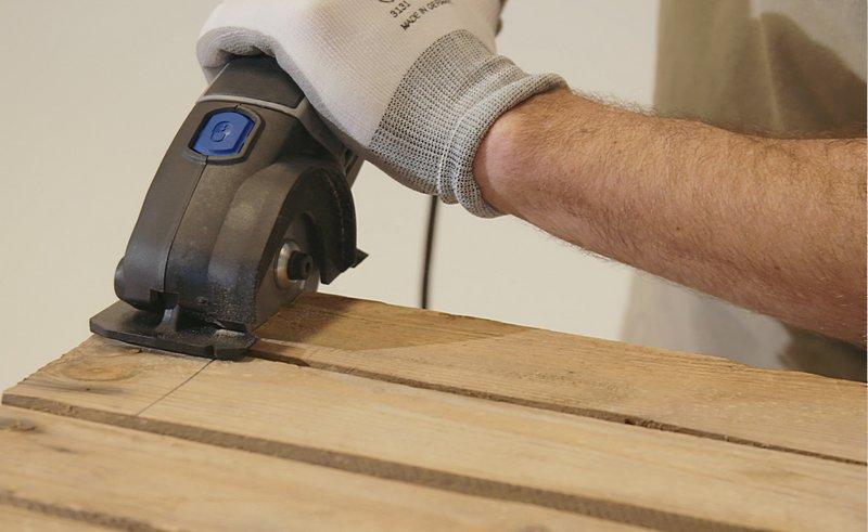 Zaag de houten planken met een Dremel DSM20 compactzaag, uitgerust met een multifunctionele carbide snijschijf.