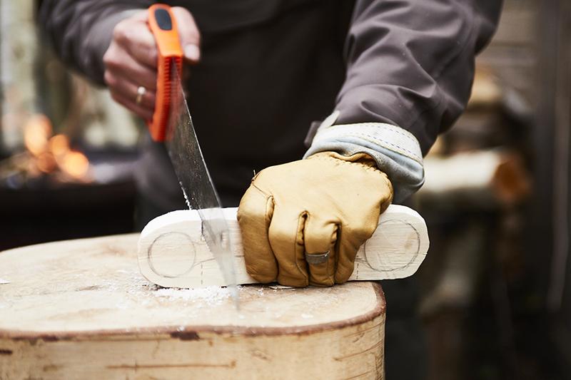 Przepiłuj drewno do miejsca wskazanego liniami, aby utworzyć szczelinę, która zapobiegnie odłamywaniu się nieodpowiednich fragmentów łyżki przy pracy siekierą.