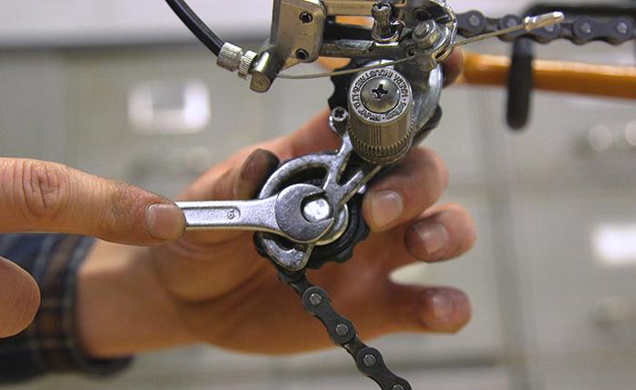 Протяните цепь через ролики и установите колесо.