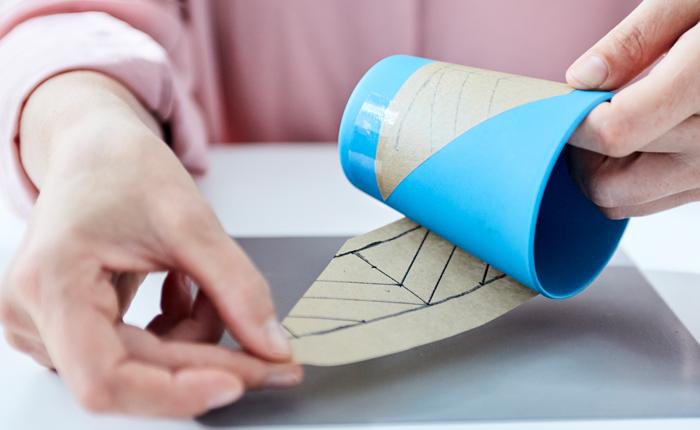 Прежде чем начинать работу с клеевым пистолетом, закрепите пергамент на многоразовом кофейном стаканчике с помощью прозрачной клейкой ленты.