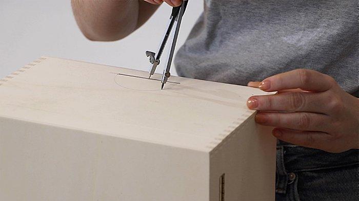 Нарисуй на коробке для кабелей полуокружности, чтобы потом вырезать их используя многофункциональный инструмент Dremel®.