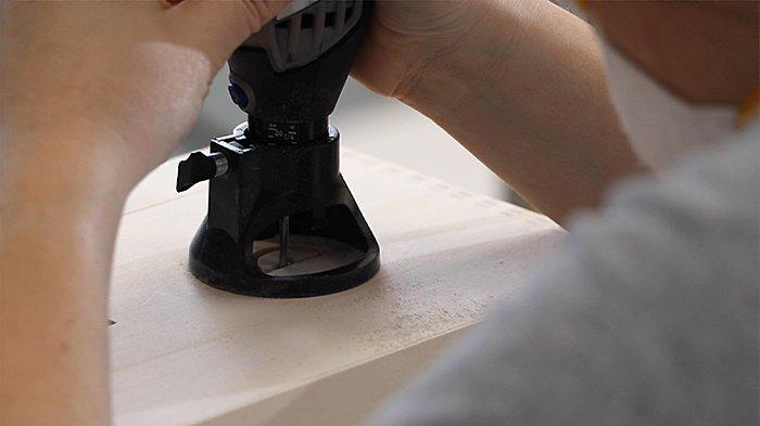 Вырежь полукруглые отверстия на своей самодельной коробке для кабелей с помощью Dremel® 3000, многоцелевого набора для резки (565) и бура (561).